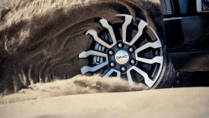 Close-up of GMC Sierra 1500 AT4 wheel kicking up sand